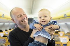 Father with his six months old baby boy in the airplane stock photography