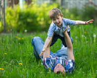 Father with his small son playing in the grass on the summer. Father with his small son playing in the grass on the summer park Royalty Free Stock Photo