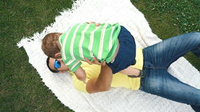 Father with his small son playing in the grass on the summer park. stock footage