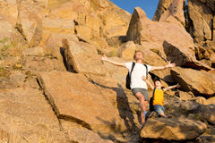 Father and his small son on a rocky mountain. Standing on a ledge with their arms open wide to the summer sunshine as they celebrate nature Stock Images