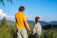 Father and his small son stand on the mountain meadow. Among a lush green grass, holding hands and admiring the view opened before them. Back view. Awesome stock image
