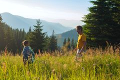 Father and his small son stands among a lush green grass. Father and his small son are standing on the mountain meadow, among a lush green grass, during sunset stock images