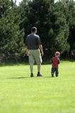 Father and his son. Father and son walk happy close together over a meadow in the summer sun Stock Photography