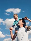 Father and his son against the cloudy sky Stock Images