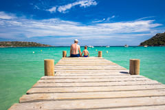 Father and his son on the bridge in Santa Giulia beach, Corsica, France Stock Images