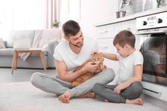Father and his son with cat. At home Stock Photo