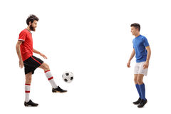 Father and his son dressed in jerseys passing a football. Full length profile shot of a father and his son dressed in jerseys passing a football isolated on royalty free stock image