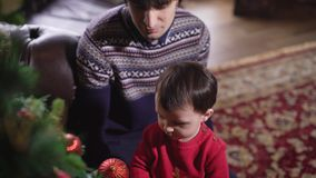 Father with his son for the first time decorate Christmas tree sitting on a beautiful carpet near a leather sofa. Little stock footage