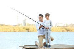 Father and his son fishing from pier. On river stock photography