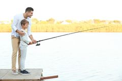 Father and his son fishing from pier. On river stock image
