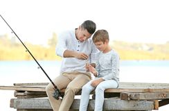 Father and his son fishing from pier. On river royalty free stock photography