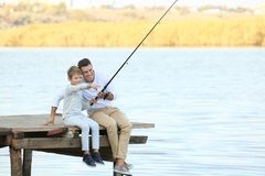 Father and his son fishing from pier. On river royalty free stock images