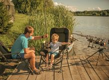 Father with his son on a fishing trip. Father with son engaged in fishing in river. Sitting on wood pontoon Royalty Free Stock Photos