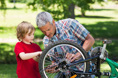Father and his son fixing a bike Stock Image