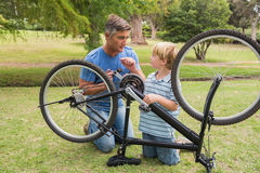 Father and his son fixing a bike Stock Images