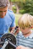 Father and his son fixing a bike Royalty Free Stock Photo