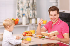 Father and his son are having fine breakfast Royalty Free Stock Photos