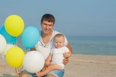 Father and his son having fun on the beach Stock Photos