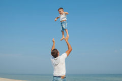 Father and his son having fun on the beach Stock Photography