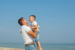 Father and his son having fun on the beach Stock Photos