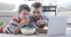 Father with son having fun watching movie on laptop stock video