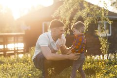 Father and his son having fun outside in summer hugging and laughing. Father taking care of his child. Father and his son having fun outside in summer hugging Royalty Free Stock Images