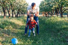 Father and his son having fun outside in summer hugging and laughing. Father taking care of his child. Father and his son having fun outside in summer hugging Stock Photos