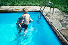 Father and his son having fun in the swimming pool. On beautiful summer day Royalty Free Stock Photography