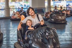 Father and his son having a ride in the bumper car at the amusem Royalty Free Stock Image