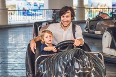 Father and his son having a ride in the bumper car at the amusement park Royalty Free Stock Image