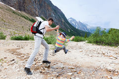 Father and his son hiking. Father helping his son to jump over stream in jasper national park Stock Images