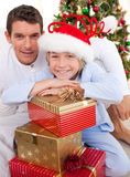 Father and his son holding Christmas presents. Portrait of a father and his son holding Christmas presents and sitting on the floor stock image