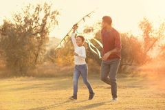 Father and his son with kite. In countryside stock photography