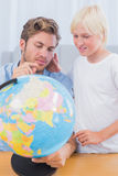 Father and his son looking at globe Royalty Free Stock Images