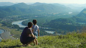 Father with his son are looking to the mountains. And river stock footage