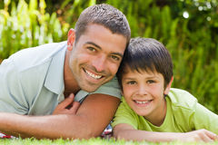 Father with his son lying down in the garden Royalty Free Stock Photo