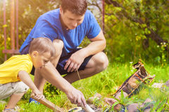 Father and His Son Making Fireplace Together Outdoors. Stock Images