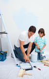 Father and his son painting in their new house stock photography