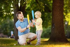 Father and his son playing baseball in park. Outdoor sport activities for family with kids royalty free stock photo
