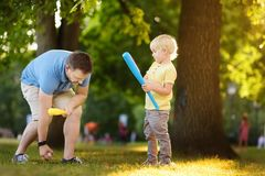 Father and his son playing baseball in park. Outdoor sport activities for family with kids stock photography