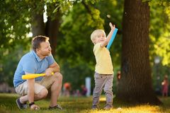 Father and his son playing baseball in park. Outdoor sport activities for family with kids royalty free stock images