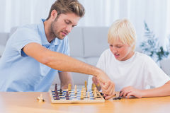 Father and his son playing chess. In living room royalty free stock images