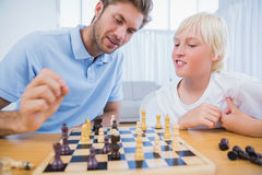 Father and his son playing chess together. In the living room stock photos