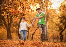 Father and his son playing with fallen leaves. In park stock image