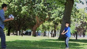 Father and his son playing football in a park