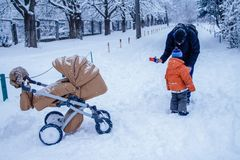 Father and his son playing outside, winter forest on the background, snowing, happy and joyful. Father, dad and his son playing outside, winter forest on the royalty free stock photography