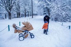 Father and his son playing outside, winter forest on the background, snowing, happy and joyful. Father, dad and his son playing outside, winter forest on the royalty free stock photo