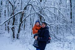 Father and his son playing outside, winter forest on the background, snowing, happy and joyful. Father, dad and his son playing outside, winter forest on the Stock Images