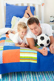 Father and his son playing with a soccer ball Stock Photography