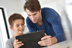 Father and his son playing on tablet Stock Photography